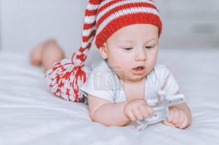 excited infant child playing with toy deer decoration in bed