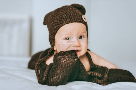 Photo for Infant child in brown knitted hat biting blanket in bed - Royalty Free Image
