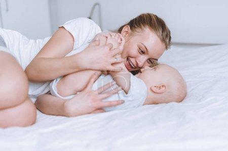 Photo pour Jeune maman heureuse et son bébé câlins dans le lit de bébé - image libre de droit