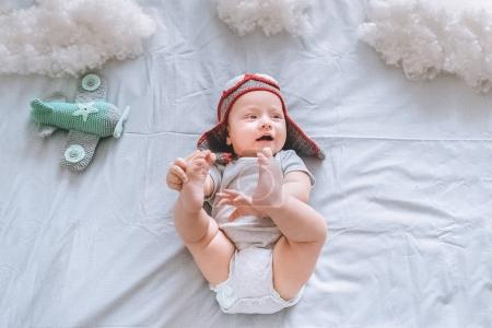 top view of dreamy infant child in pilot hat with toy plane surrounded with clouds made of cotton in bed