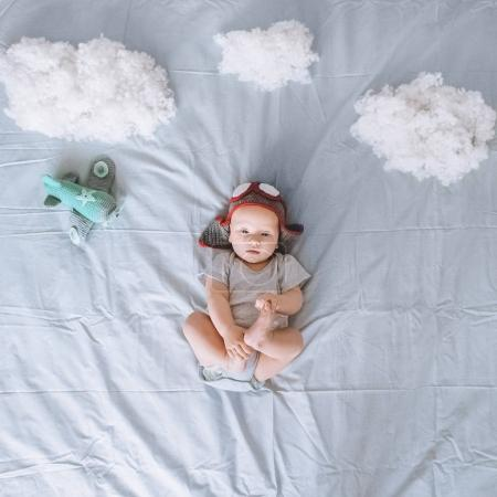 top view of dreamy infant child in knitted pilot hat with toy plane surrounded with clouds made of cotton in bed