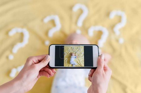 cropped shot of mother taking top view photo of child sleeping surrounded with question marks on yellow bed