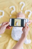 cropped shot of mother taking top view photo with smartphone of child sleeping in bed surrounded with question marks