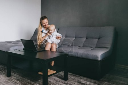 young mother and her infant child looking at laptop while sitting on couch at home