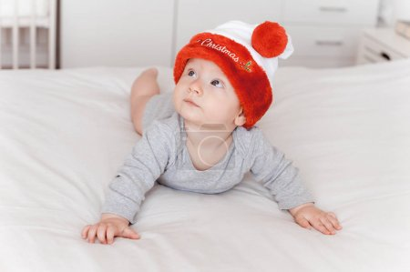 Photo for Portrait of adorable infant child in santa hat lying on bed and looking up - Royalty Free Image