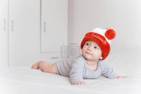 portrait of little infant child in santa hat lying on bed and looking away