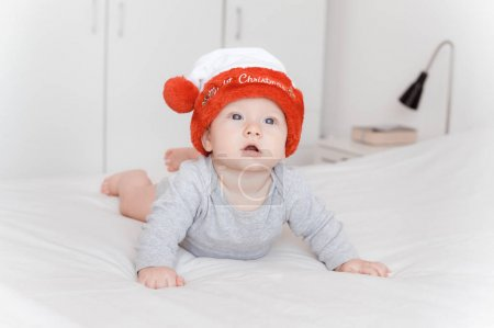 portrait of little infant child in santa hat lying on bed