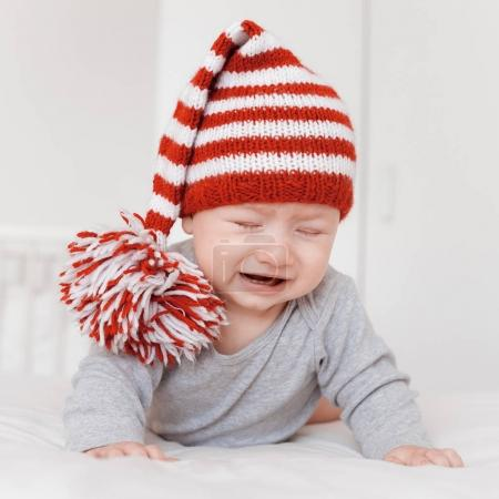 portrait of little crying infant child in funny knitted hat lying on bed