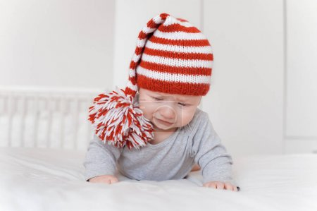 portrait of little infant child in knitted hat lying on bed and looking down
