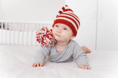portrait of beautiful infant child in knitted hat lying on bed