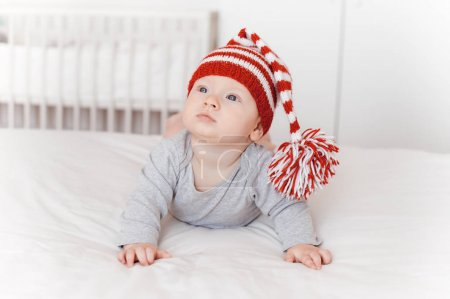 portrait of cute infant child in knitted hat lying on bed
