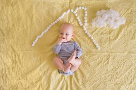 adorable funny infant child lying under house roof made of cotton balls and cotton cloud on bed
