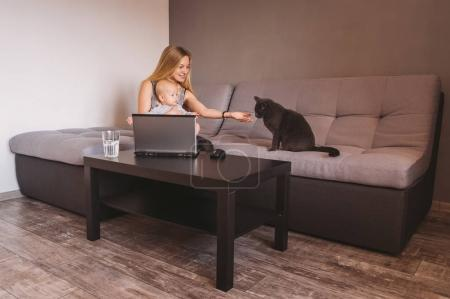 happy mother and cute little child looking at black cat while sitting on sofa and using laptop