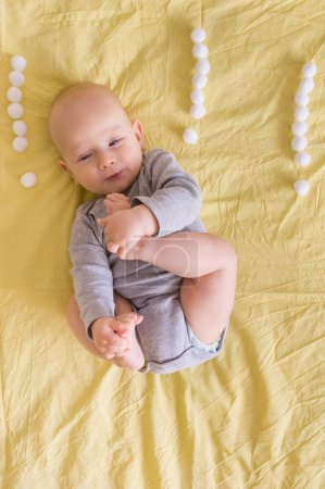 top view of infant child surrounded with exclamation marks made of cotton balls in bed