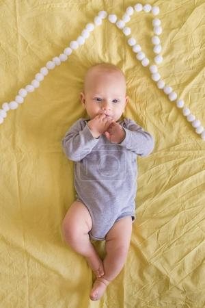 top view of beautiful infant child under house roof made of cotton balls in bed
