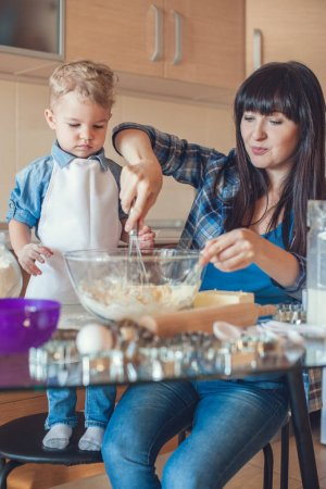 mother whisking dough in glass bowl