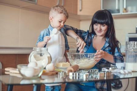 son holding measuring cup and mother whisking dough