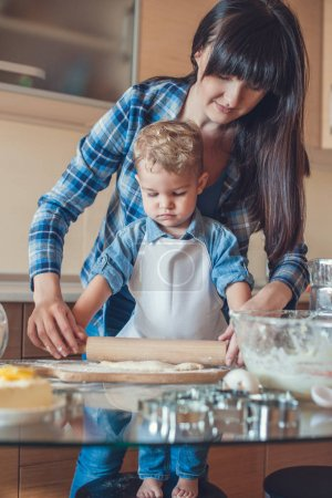 Photo for Mother and son rolling dough with rolling pin - Royalty Free Image
