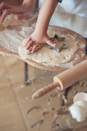 cropped image of son making cookies with dough molds