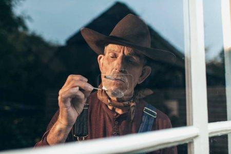 Senior man lighting cigarette