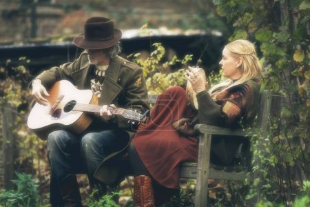 Man and woman playing music in garden