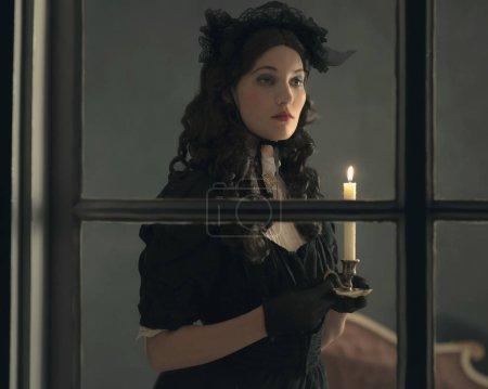 Photo pour Femme victorienne rétro en robe noire tenant chandelier et debout derrière la fenêtre . - image libre de droit