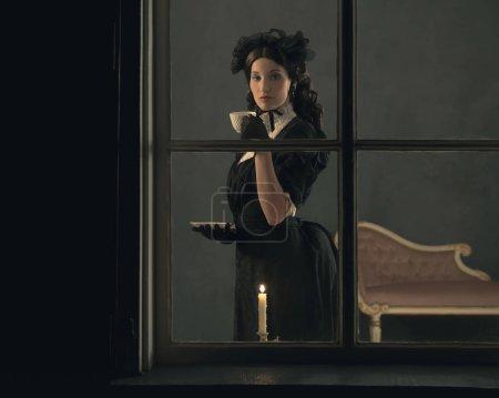 Photo pour Vintage victorienne fille boire tasse de thé derrière la fenêtre . - image libre de droit