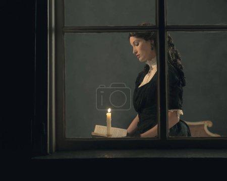 Photo pour Rétro victorienne livre de lecture femme aux chandelles derrière la fenêtre . - image libre de droit