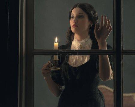 Photo pour Rétro victorienne femme tenant chandelier regardant par la fenêtre pluvieuse . - image libre de droit