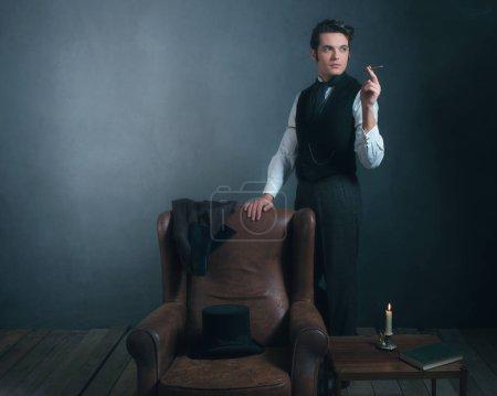 Photo pour Vintage victorien homme debout à côté de chaise fumer cigarette . - image libre de droit