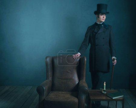 Photo pour Rétro dickens style homme debout avec canne à côté de chaise en cuir . - image libre de droit