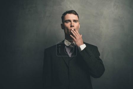 Photo pour Retro Années 1920 gangster anglais en costume fumer cigarette . - image libre de droit