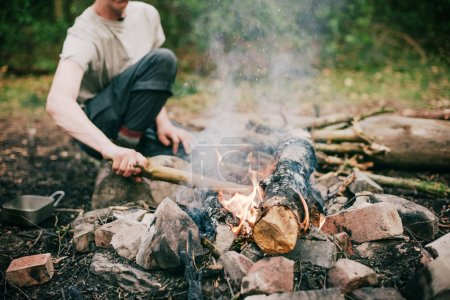 man moving wooden log in campfire