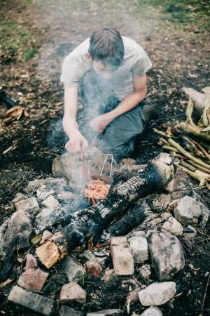 tourist stirring meal in frying pan