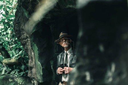 Explorer standing with binoculars