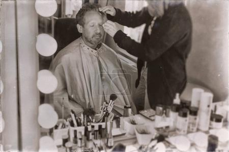 Photo for Old sepia photo of man sitting in front of mirror and getting makeup - Royalty Free Image