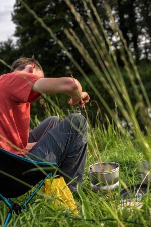 Photo pour Adolescent garçon assis à camping et ouverture bouteille - image libre de droit