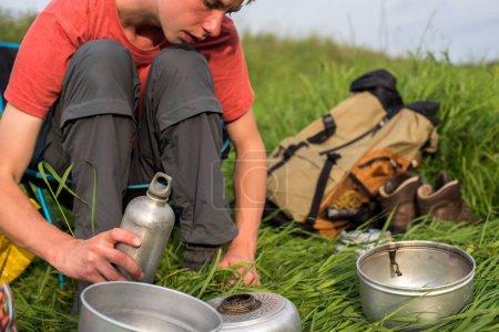 Photo pour Adolescent assis au camping et remplissage lampe à alcool - image libre de droit