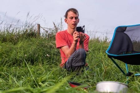 Photo pour Photo prise adolescent avec smartphone au camping - image libre de droit