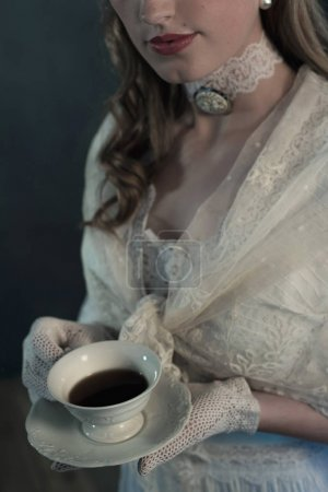 Photo for Young victorian woman holding cup of tea - Royalty Free Image