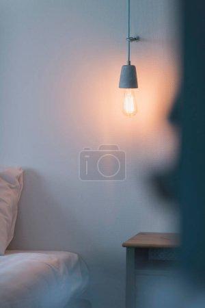 Photo pour Ampoule vintage suspendue au mur dans la chambre - image libre de droit