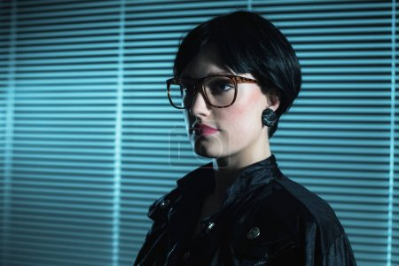 young woman in front of blinds