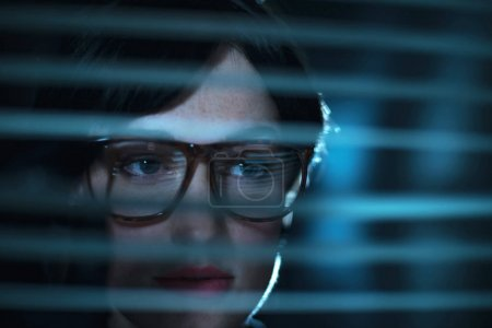 woman in glasses looking through blinds