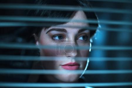 woman looking through blinds.