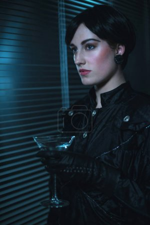young woman holding cocktail glass