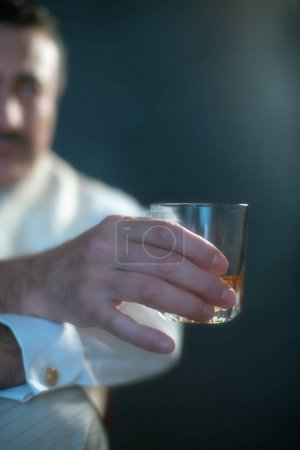 man holding glass of whiskey.