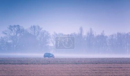 Car driving in rural landscape