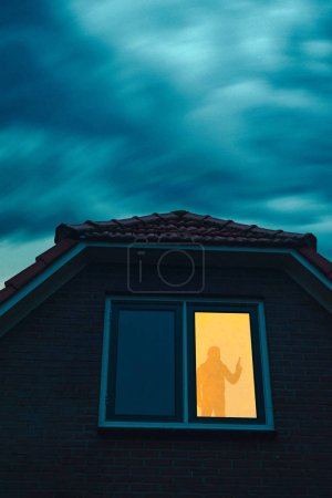 Photo for Burglar with handgun in ominous house with illuminated window under stormy sky at dusk. - Royalty Free Image