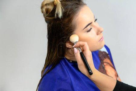 Photo pour Photo prise au studio d'un maquilleur par un esthéticien coiffeur. Créer un maquillage et des coiffures magnifiques, rajeunissant la peau du visage. Le professionnel travaille avec des outils spéciaux. - image libre de droit