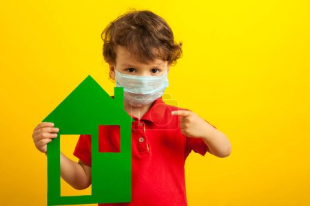 stay home. A boy, a curly-haired kid in a medical mask holds a green cardboard house in his hands and points a finger at it on a bright yellow background, studio. coronavirus pandemic.